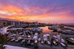 坐在户外咖啡馆和享受惊人的日落和凯里尼亚旅游港口的美丽的景色游人 免版税图库摄影