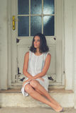 坐在房子前面的孤独的哀伤的赤足女孩在春天 库存图片