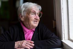 坐在房子里的一名年长妇女在窗口附近 画象 库存照片