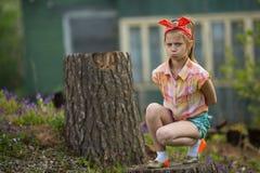 坐在房子附近的一种坏心情的小女孩在村庄 自然 图库摄影