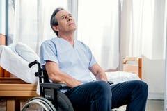 坐在房间的轮椅的年长人在医院 免版税库存图片