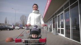 坐在手推车的逗人喜爱的微笑的男孩 幸福家庭去购物 股票视频