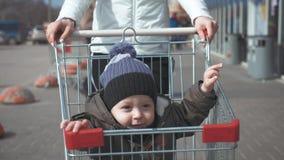 坐在手推车的逗人喜爱的微笑的男孩 幸福家庭去购物 影视素材