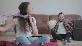 坐在手提箱和一个有胡子的人的逗人喜爱的妇女在尝试的沙发旁边坐准备包装的事 股票视频
