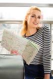 坐在手提箱附近在火车站和拿着地图的镶边毛线衣的旅游白肤金发的女孩 免版税库存照片
