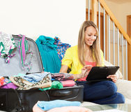 坐在手提箱附近的妇女,当使用数字式片剂时 库存图片
