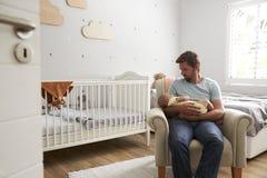 坐在托儿所椅子举行睡觉的小儿子的父亲 免版税库存图片