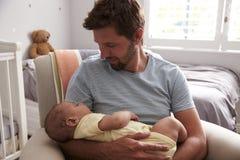 坐在托儿所椅子举行睡觉的小儿子的父亲 免版税图库摄影