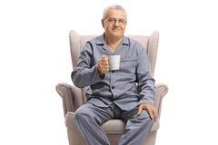 坐在扶手椅子和拿着一个杯子热的饮料的睡衣的年长人 库存照片