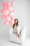 坐在扶手椅子和拿着一束桃红色气球的妇女 免版税库存图片