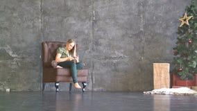 坐在扶手椅子和看电话的少妇 股票录像