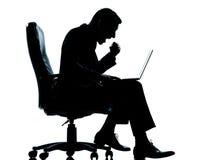 坐在扶手椅子的一商人计算机计算的成功 库存图片