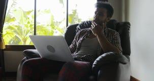 坐在扶手椅子的人使用便携式计算机键入的在家工作,人冲浪的互联网愉快微笑 股票录像