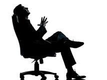 坐在扶手椅子的商人放松 免版税库存图片