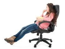 坐在扶手椅子的懒惰妇女吃玉米花,被隔绝在白色 免版税库存照片