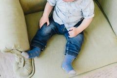 坐在扶手椅子的逗人喜爱的矮小的小孩男孩 库存照片