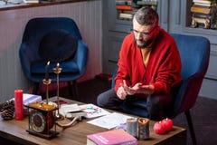 坐在扶手椅子看书和做实践的有胡子的占卜师 免版税库存图片