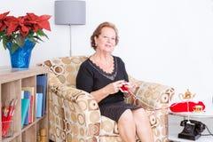 坐在扶手椅子编织的年长夫人 免版税库存照片