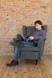 坐在扶手椅子阅读书的人 库存图片