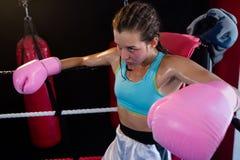 坐在拳击台的角落的年轻女性拳击手 库存图片