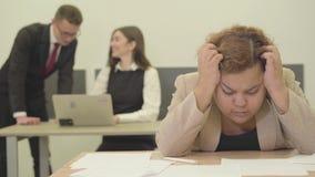 坐在拿着她的头用手的前景的桌上的画象紧张的妇女,她有麻烦在工作 股票视频