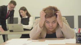 坐在拿着她的头用手的前景的桌上的紧张的妇女,她有麻烦在工作 ?? 股票录像