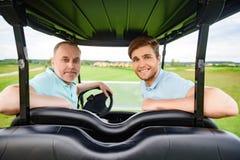 坐在推车的两位高尔夫球运动员 免版税库存图片