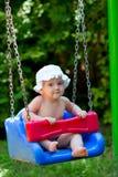 坐在摇摆的逗人喜爱的女婴 免版税库存图片