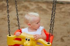 坐在摇摆的逗人喜爱的白肤金发的女婴 免版税库存照片
