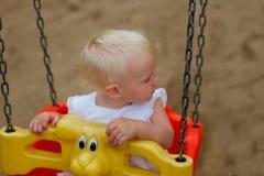 坐在摇摆的逗人喜爱的白肤金发的女婴 库存图片