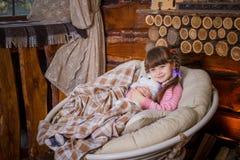 坐在摇椅的小女孩在壁炉附近 免版税库存图片