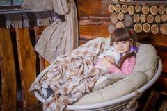 坐在摇椅的小女孩在壁炉附近 免版税图库摄影