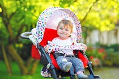坐在摇篮车或婴儿推车和等待妈妈的逗人喜爱的健康矮小的美丽的女婴 愉快的微笑的孩子与 免版税库存图片