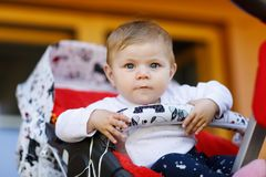 坐在摇篮车或婴儿推车和等待妈妈的逗人喜爱的矮小的美丽的女婴 有蓝眼睛的愉快的微笑的孩子 免版税库存图片