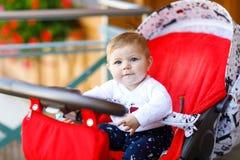 坐在摇篮车或婴儿推车和等待妈妈的逗人喜爱的矮小的美丽的女婴 有蓝眼睛的愉快的微笑的孩子 免版税图库摄影