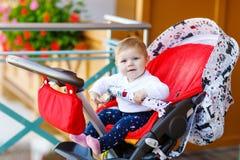 坐在摇篮车或婴儿推车和等待妈妈的逗人喜爱的矮小的美丽的女婴 有蓝眼睛的愉快的微笑的孩子 库存照片