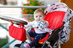 坐在摇篮车或婴儿推车和等待妈妈的逗人喜爱的矮小的美丽的女婴 有蓝眼睛的愉快的微笑的孩子 库存图片