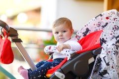 坐在摇篮车或婴儿推车和等待妈妈的逗人喜爱的矮小的美丽的女婴 有蓝眼睛的愉快的微笑的孩子 图库摄影