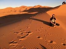 坐在撒哈拉大沙漠的嬉皮人,某处在摩洛哥 库存照片