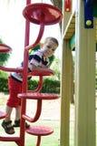 坐在操场的严肃的小男孩 免版税库存照片