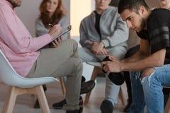 坐在支持组上会议的傲慢少年,当喂时 免版税库存图片