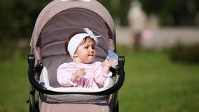 坐在支架和饮用奶的逗人喜爱的婴孩女孩在公园 股票视频