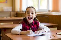 坐在教室和愉快地呼喊的书桌的微笑的白种人女孩 年轻前女小学生画象  愉快的学生 库存图片