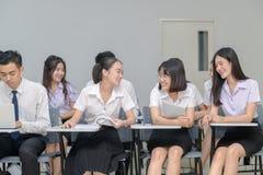 坐在教室和谈话的亚裔学生 图库摄影