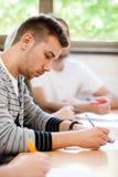 坐在教室的男性大学生 免版税库存图片