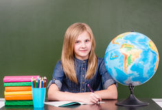 坐在教室的青少年的女孩在空的绿色黑板附近 免版税图库摄影