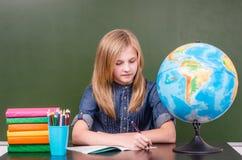 坐在教室的青少年的女孩在空的绿色黑板附近 免版税库存照片