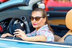坐在敞篷车汽车wi的太阳镜的年轻俏丽的妇女 免版税库存照片