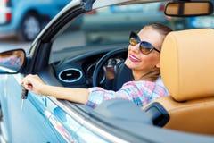 坐在敞篷车汽车wi的太阳镜的年轻俏丽的妇女 免版税库存图片