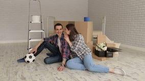 坐在新的公寓的容忍的愉快的年轻夫妇在纸板箱中 股票视频